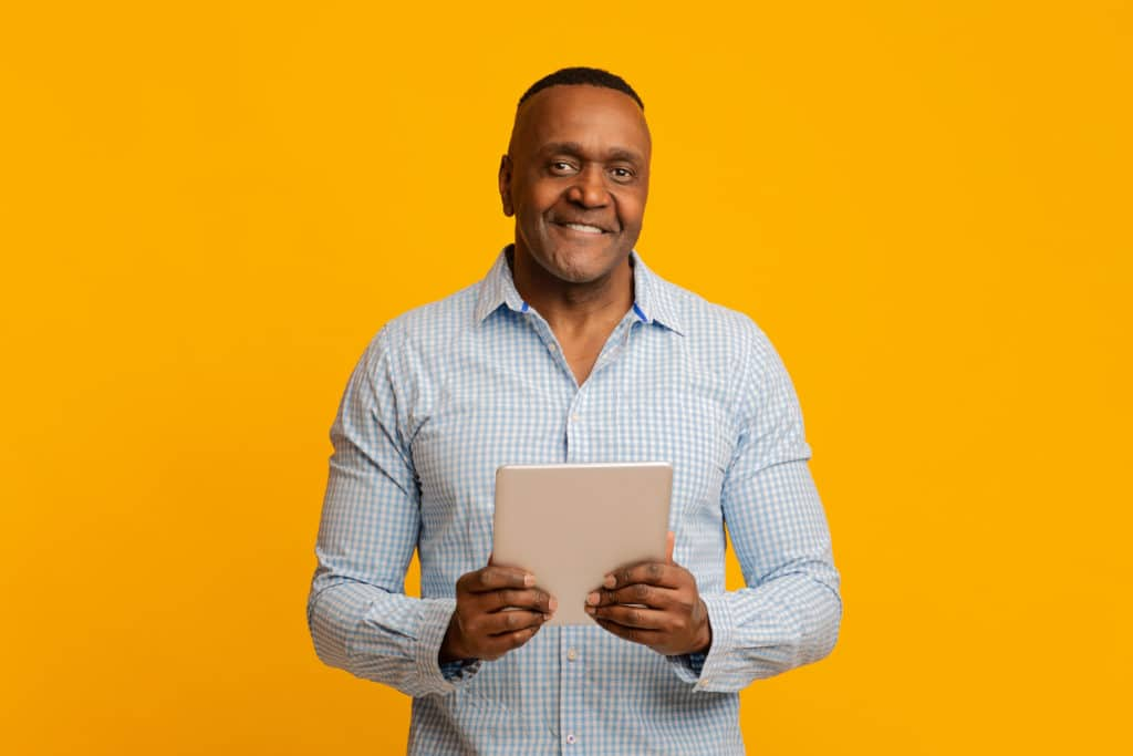 Mature African Businessman Holding Digital Tablet And Smiling, Orange Studio Background